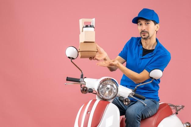 パステル調の桃の背景に注文を示すスクーターに座っている帽子をかぶった宅配便の男性のトップビュー