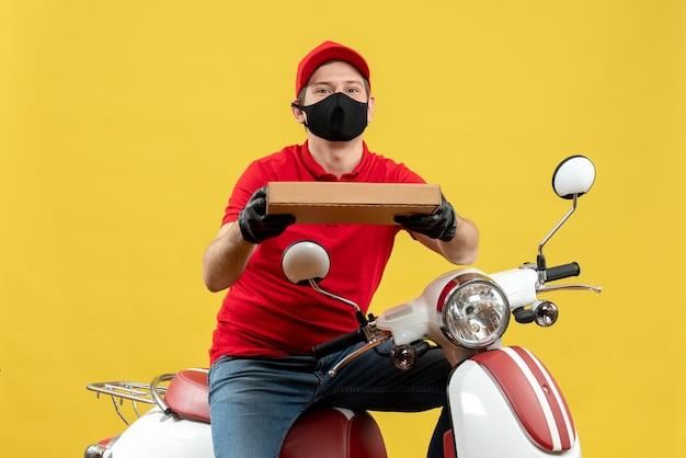 注文を与えるスクーターに座っている医療用マスクで赤いブラウスと帽子の手袋を着用して宅配便の男の上面図