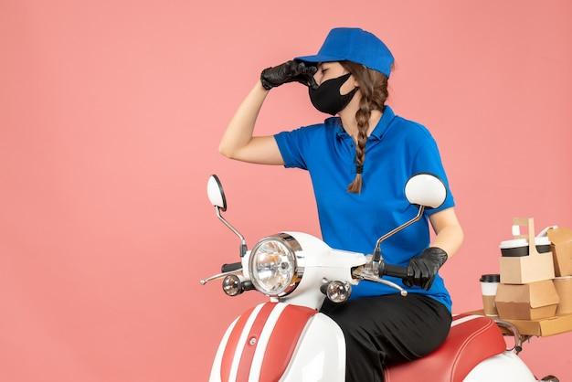 파스텔 복숭아 배경에 나쁜 냄새 제스처를 만드는 주문을 제공하는 스쿠터에 앉아 의료 마스크와 장갑을 착용하는 택배 여자의 상위 뷰