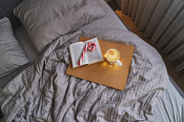 Вид сверху на уютную спальню с кроватью в бежевых тонах, кофейной кружкой, мятой и книгой. ленивое рождественское утро в постели