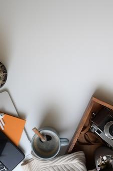 ラップトップコンピューター、カメラ、コーヒーカップ、事務用品と居心地の良いワークスペースの平面図