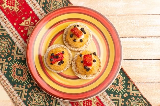 Вид сверху крекеров и пирожных внутри цветной тарелки
