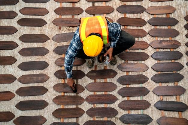 장인이나 페인트 브러시의 상위 뷰는 건설 현장의 나무 판자에 페인트나 바니시를 적용합니다.