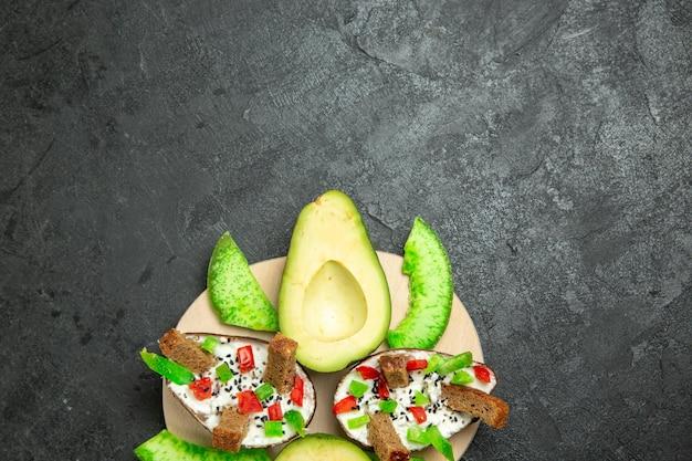 灰色の表面にパンとコショウと新鮮なアボカドを添えたクリーミーなアボカドの上面図