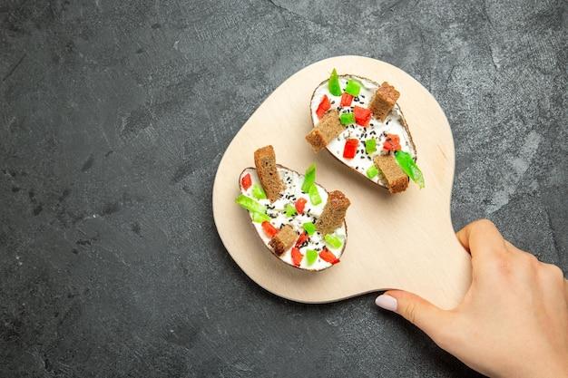 灰色の表面にスライスしたピーマンとパンの部分を持つクリーミーなアボカドの上面図