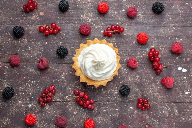 茶色の机のいたるところに広がるさまざまなベリーと一緒にクリーミーでおいしいケーキの上面図、ベリーフルーツクリームベイクビスケット