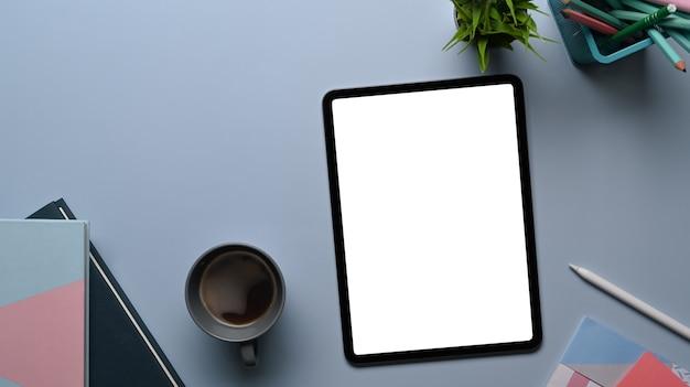 회색 테이블에 모의 디지털 태블릿, 노트북, 커피 컵, 식물이 있는 창의적인 디자이너 또는 세련된 작업 공간의 상위 뷰.