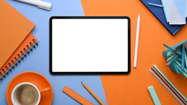 Взгляд сверху творческого дизайнерского рабочего места с цифровым планшетом и канцелярскими принадлежностями на двухцветном синем и оранжевом фоне.