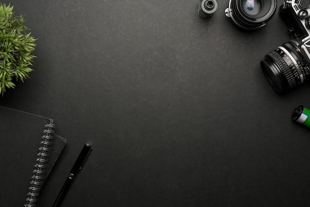 Вид сверху на творческий плоский черный стол с канцелярскими принадлежностями для камеры и копией пространства