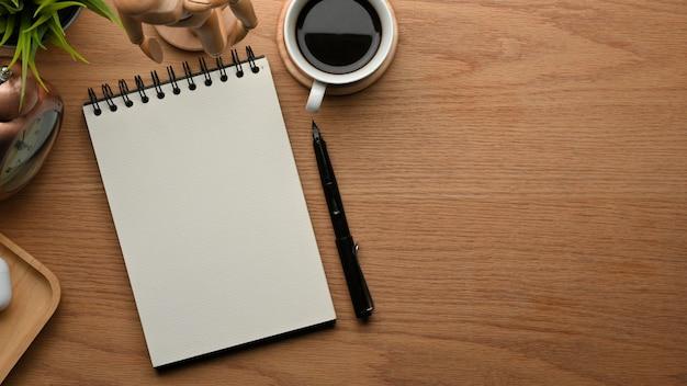 Вид сверху творческой плоской рабочей области с блокнотом, ручкой, кофейной чашкой и украшениями на деревянном столе