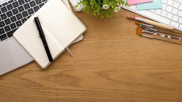 文房具のラップトップ用品と木製のテーブルのコピースペースと創造的なフラットレイワークスペースの上面図