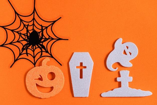 オレンジ色の紙のテーブルの背景に創造的なハロウィーンのコンセプトの装飾の上面図。