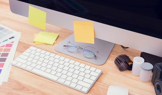 大型デスクトップコンピューターを備えたクリエイティブテーブルの上面図。グラフィックデザインのための作業場所。
