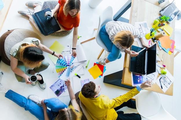 사무실 공간에서 비공식 회의 데 창조적 인 노동자의 상위 뷰. 컬러 샘플, 회의실 레이아웃, 랩톱, 소모품으로 바닥에서 작업하는 건축가 및 인테리어 디자이너. 팀워크 개념.