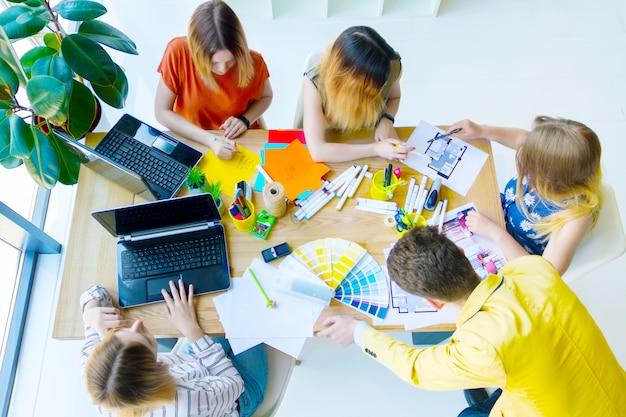 オフィスで会議を行っている創造的な労働者の平面図です。テーブルに座りながら、色見本、部屋のレイアウト、ラップトップを使ってデザインプロジェクトについて話し合う建築家とインテリアデザイナー。チームワークの概念。