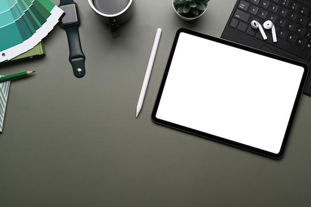 스마트 시계, 휴대폰, 무선 키보드, 색상 견본, 이어폰 및 복사 공간이 녹색 테이블에 있는 창의적인 작업 공간의 상위 뷰.