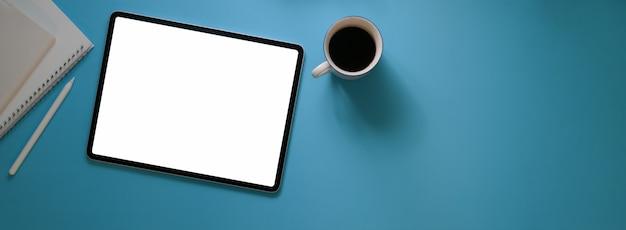 빈 화면 태블릿, 커피 컵, 일기 노트북 및 복사 공간이있는 창조적 인 작업 공간의 상위 뷰