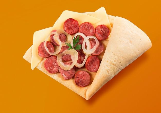 オレンジ色の背景にタマネギ、パセリ、チーズとペパロニソーセージのスライスとクレープまたはファインパンケーキの上面図。 Premium写真