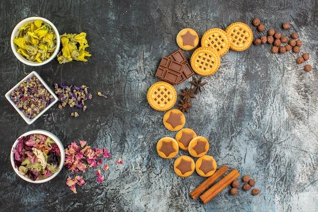 Вид сверху полумесяца из конфет и чаш с сухими цветами на серой земле