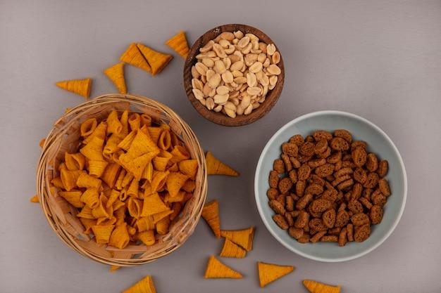 Вид сверху хрустящих закусок из жареной кукурузы в форме конуса на ведре с кедровыми орехами на деревянной миске с ржаными сухарями на миске