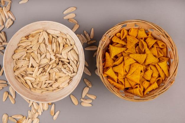 Вид сверху хрустящих закусок из жареной кукурузы в форме конуса на ведре с белыми семечками на миске