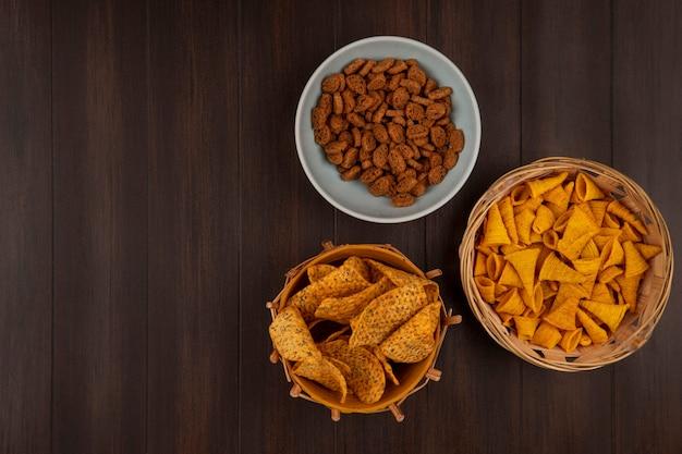 Вид сверху хрустящих вкусных ржаных сухарей на миске с пряными чипсами на ведре с кукурузными закусками на ведре на деревянном столе с копией пространства