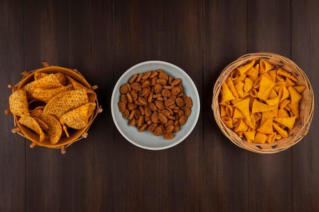Вид сверху на хрустящие вкусные ржаные сухарики на миске с пряными чипсами на ведре с кукурузными закусками на ведре на деревянном столе