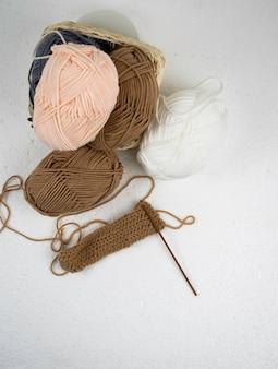 나무 크로 셰 뜨개질 후크와 갈색 원사 공으로 크로 셰 뜨개질 작업의 상위 뷰,