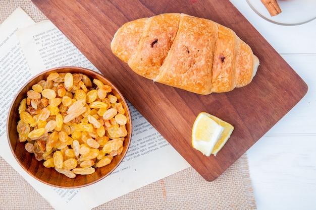 Вид сверху круассан с кусочком лимона на деревянной разделочной доске и сушеный изюм в деревянной миске на белом