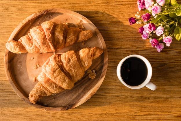 木製テーブルの背景にクロワッサンとコーヒーカップのトップビュー。