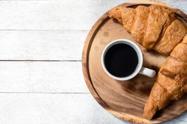 木製のテーブルの背景にクロワッサンとコーヒーのトップビュー。テキストの空き領域