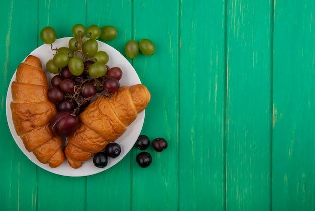 Вид сверху круассанов и винограда в тарелке на зеленом фоне с копией пространства