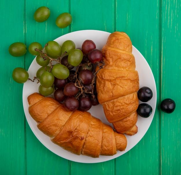 녹색 배경에 접시에 크루아상과 포도의 상위 뷰