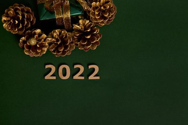 Вид сверху обрезанного рождественского подарка в зеленой оберточной бумаге с золотым бантом и сосновыми шишками, окрашенными в золотой цвет, деревянными цифрами, символизирующими 2022 год, выложенными на темном фоне с копией пространства