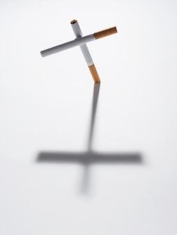 Вид сверху крест знак из сигареты с ним тень на белом фоне