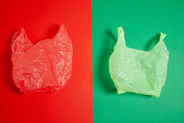 2色の背景に配置されたしわくちゃの赤と緑のビニール袋の上面図