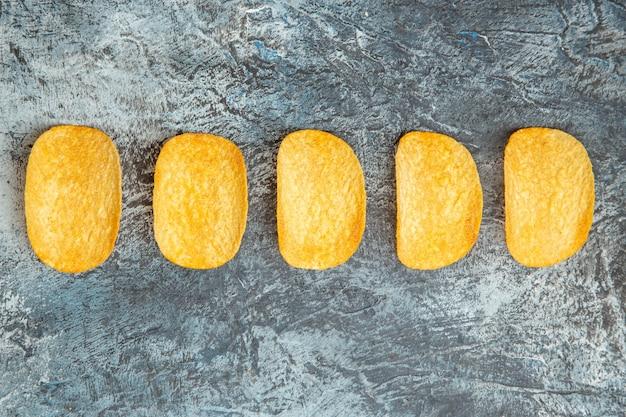 회색 배경에 연속으로 늘어선 바삭 바삭한 구운 5 칩의 상위 뷰