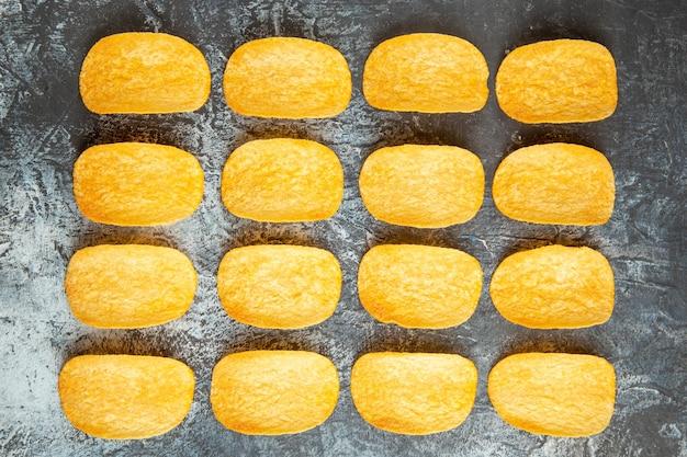 Вид сверху на хрустящие запеченные пять чипсов, выстроенных рядами на сером фоне