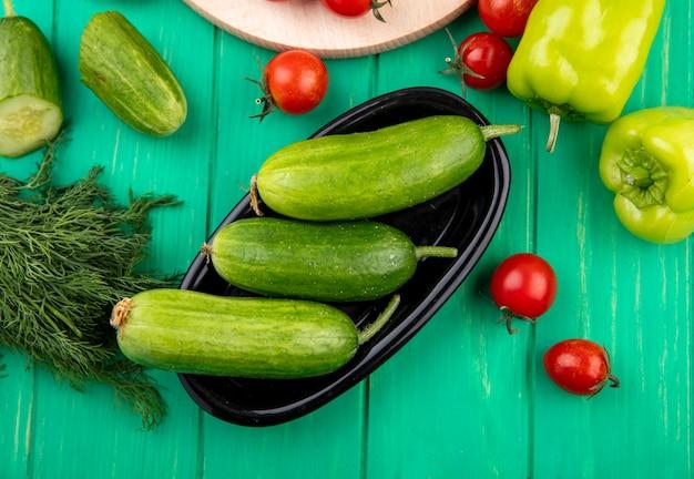 緑の周りのボウルとコショウトマトディルでキュウリのトップビュー