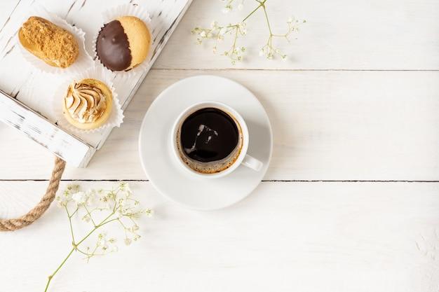 コピースペースのある木製トレイにブラックコーヒーとミニケーキのカップの上面図。朝の朝食の構成。