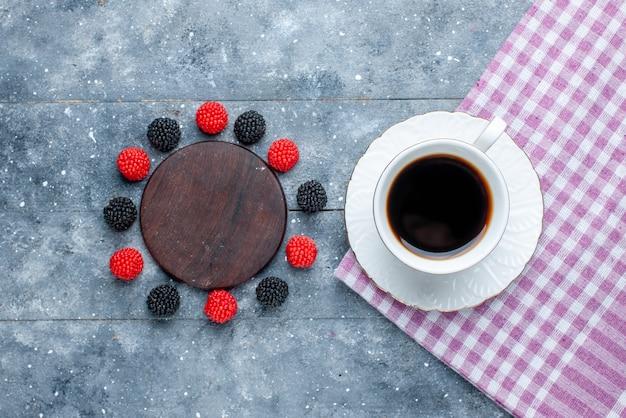 Вид сверху чашки кофе вместе с ягодами конфитюра на сером столе, сладкой выпечки, сахарного торта