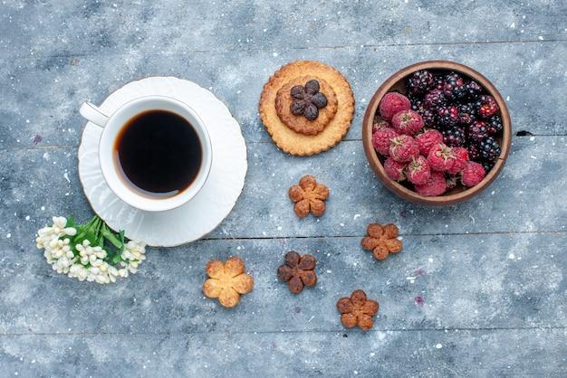 Вид сверху на чашку кофе вместе с ягодами печенья на сером, сладком сахаре, выпечке, печенье, печенье