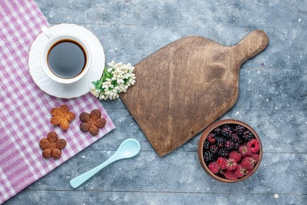 灰色の木製の甘い砂糖焼きペストリークッキービスケットのクッキーベリーと一緒に一杯のコーヒーの上面図