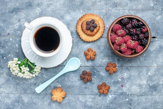 Вид сверху на чашку кофе вместе с маленьким печеньем и ягодами на сером деревянном сладком бисквитном печенье
