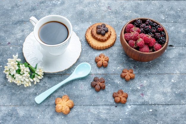 灰色の木製の甘い砂糖焼きペストリークッキービスケットに小さなクッキーと新鮮なベリーと一緒に一杯のコーヒーの上面図