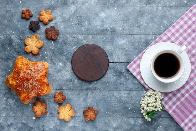 Вид сверху на чашку кофе вместе с пирожным и вкусным печеньем на сером столе, сладкую выпечку, сахарный торт