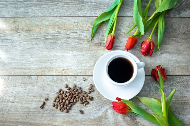 一杯のコーヒーと豆と赤いチューリップの花束、コピースペースの上面図。