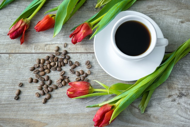 Вид сверху на чашку кофе и бобов и букет красных тюльпанов