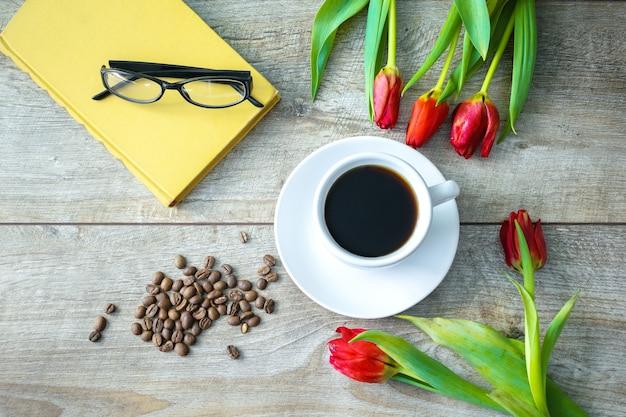 一杯のコーヒーと豆、赤いチューリップの花束、本の上面図
