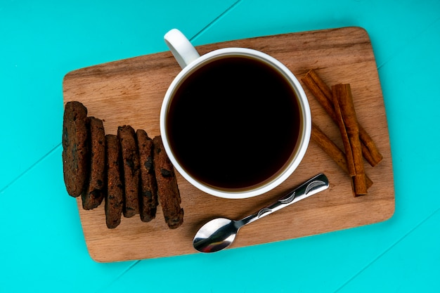 Вид сверху чашку кофе и печенье с ложкой на разделочную доску на синем фоне